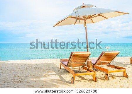 Umbrella and beach chair with beautiful tropical beach - summer vacation background #326823788