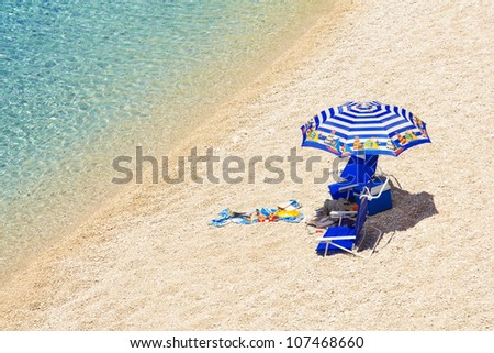 Umbrella and beach chairs at Porto Katsiki beach, Lefkada, Greece - stock photo