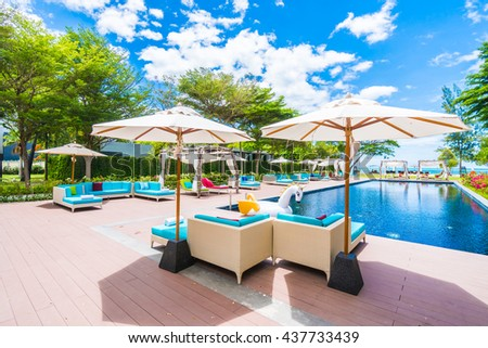 Umbrella and chair around swimming pool in beautiful luxury hotel resort for holiday vacation concept background #437733439
