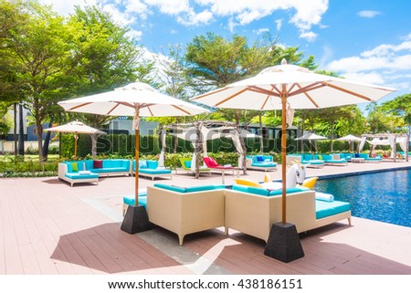 Umbrella and chair around swimming pool in beautiful luxury hotel resort for holiday vacation concept background #438186151