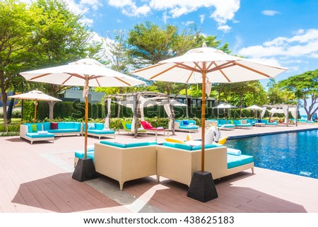 Umbrella and chair around swimming pool in beautiful luxury hotel resort for holiday vacation concept background #438625183