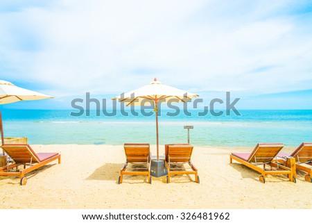 Umbrella and chair on beautiful tropical beach - summer vacation background #326481962