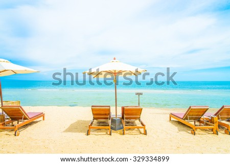 Umbrella and chair on beautiful tropical beach - summer vacation background #329334899