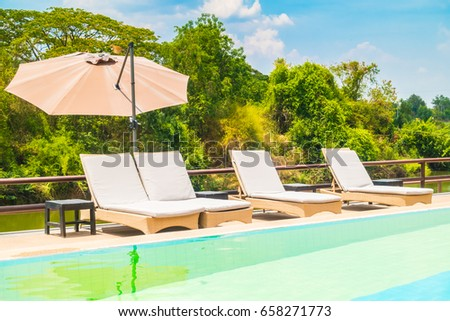 Umbrella and chair with swimming pool and outdoor view around hotel and resort #658271773