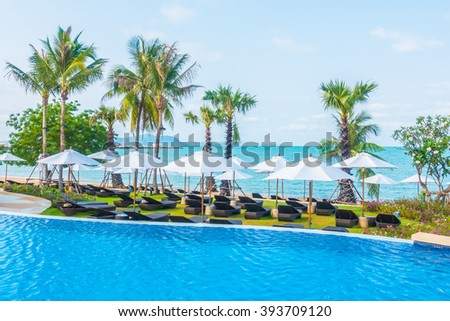 Umbrella and empty chair around swimming pool in hotel resort - Boost up color Processing #393709120