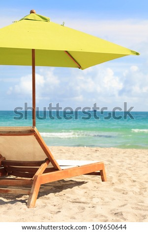 Umbrella and lounge chair along the shoreline of Miami Beach.