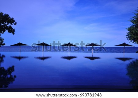 Umbrella in pool with seascape background with blue tone #690781948