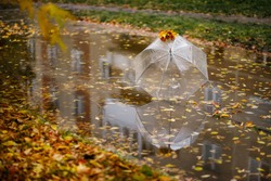 Umbrella on rainy day - The raindrops falling on an umbrella which put on the ground. Autumn concept. Rainy autumn with fallen leaves.
