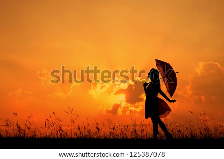 Umbrella woman stand and sunset silhouette - stock photo