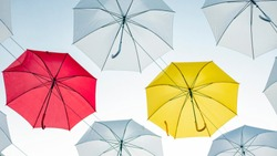 Umbrellas against the blue sky. White, yellow and red umbrella
