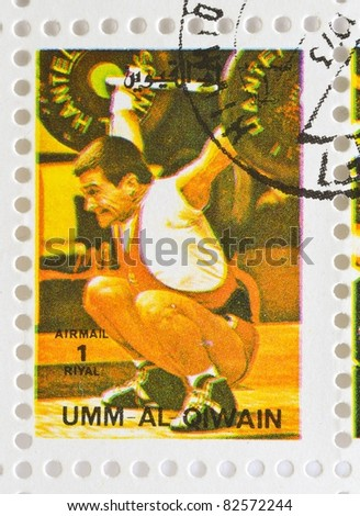 UMM AL-QIWAIN - CIRCA 1973: a stamp from Umm Al-Qiwain shows image of a weightlifter, circa 1973