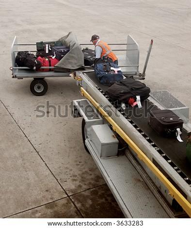 Un hombre es equipaje del cargamento sobre el aeroplano - stock photo