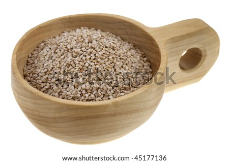 un-hulled sesame seeds in a rustic wooden bowl (scoop) isolated on white