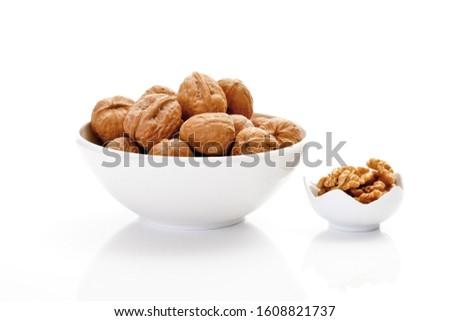 Un-shelled walnuts and shelled walnut kernels in porcelain bowls