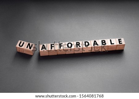 unaffordable to un affordable- words from wooden blocks with letters, too expensive concept, top view gray background