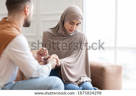 Unanswered Love. Unhappy Muslim Woman Saying No To Marriage Proposal Of Her Boyfriend, Holding Hands Sitting On Sofa At Home. Relationship Problem, Forced Marriage Concept. Selective Focus