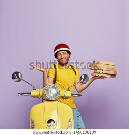 Unaware cheerful delivery man doesnt know right customer address, holds stack of carton pizza boxes, poses near motorbike, wears yellow t shirt and headgear. Service, transportation, delivery concept