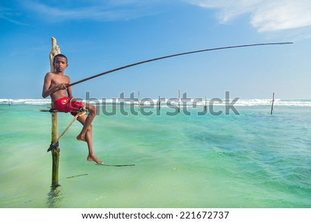 UNAWATUNA, SRI LANKA - MARCH 9, 2014: Young stilt fisherman at Hikkaduwa Beach. Most real stilt fishermen have been long gone. Today it's mainly young boys posing as stilt fishermen for tourists. #221672737