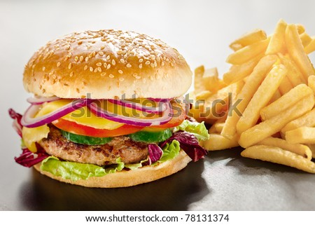 Unbearable desire. A closeup of a tempting tasty burger with red onion and vegs along with yummy french fries.