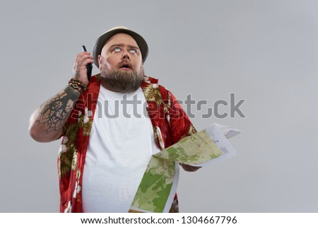 0b9fa4004 Tired fat bearded traveler in Hawaiian shirt looking at the sky and ·  Isolated on the grey background ...