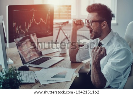 Unbelievable growth. Happy young businessman in formalwear shouting and gesturing while using computer in the office