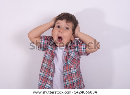 Unbelievable! Portrait of little boy holding hands on head, screaming with frightened expression. Close up of funny boy being shocked or amazed. Child's big eyes widened.