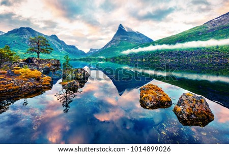 Unbelievable summer sunrise on Innerdalsvatna lake. Colorful morning scene in Norway, Europe. Beauty of nature concept background. Artistic style post processed photo. Orton Effect.