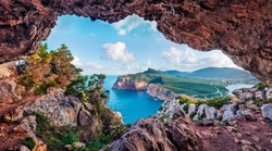 Unbelievable summer view of Caccia cape from the small cave in the cliff. Marvelous morning scene of Sardinia island, Italy, Europe. Aerial Mediterranean seascape. Beauty of nature concept background.