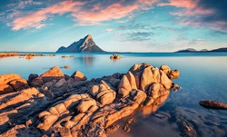 Unbelievable sunset with Tavolara mountain on background. Wonderful summer seascape of Mediterranean Sea, Porto Taverna beach, Sardinia island, Italy, Europe. Beauty of nature concept background.