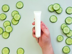 Unbranded white squeeze cream tube with long nozzle and bronze screw cap in a man's hand. Bottle for branding and fresh cucumber slices on light green background. Top view, mockup. Copy space.