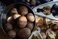 Unbroken walnuts in a round copper bowl and cracked shells.