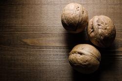 Unbroken walnuts on a wooden background