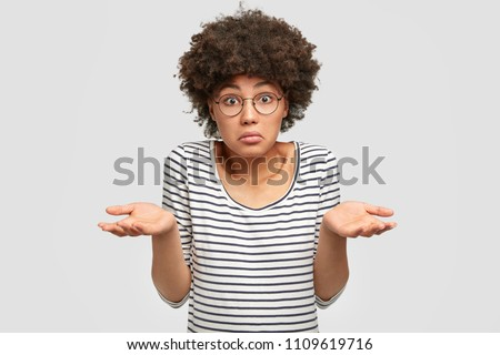 Uncertain African American female with dark skin, shruggs shoulders and asks something, has clueless expression, wears glasses and striped sweater, isolated on white background. Woman faces dilemma