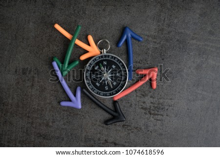 Uncertain alternative path or multiple life direction concept, compass at the center with magnet arrows pointing random multi directions on dark black chalkboard cement wall. #1074618596