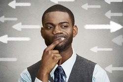 Uncertain guy looking at arrows. Man full of doubts hesitation. Closeup portrait puzzled business man thinking deciding something confused unsure isolated grey wall background. Emotion face expression