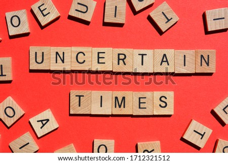 Uncertain Times, words in 3d wooden alphabet letters isolated on red background, surrounded by random wood letters