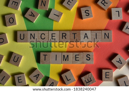 Uncertain Times, words in wooden letters surrounded by random alphabet blocks on a colorful background Stock photo ©
