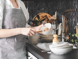 Uncertain woman in gray apron washes dishes with wooden brush near sink in kitchen. Front view