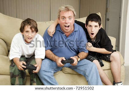 Uncle playing video games with his nephews.  Could also be dad and sons.