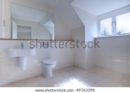Uncluttered modern chic bathroom with large mirror, tiled walls, wall mounted sink and toilet.