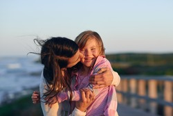 Unconditional love between mother and daughter hugging and embrace with a kiss and cuddle outdoors having fun