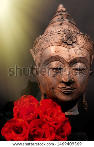Unconditional love. Spiritual enlightenment. Traditional Buddha head and red roses with divine light. Spirituality and mindfulness. Deep Buddhist meditation. Religious contemplation of God and heaven.