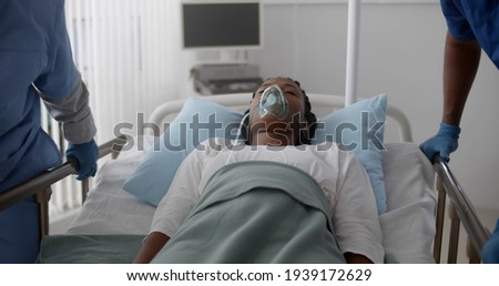 Unconscious african patient with oxygen mask on gurney stretcher bed pushed by medical team. Doctors in protective gloves pushing hospital bed with afro sick woman in hospital ward Stockfoto ©