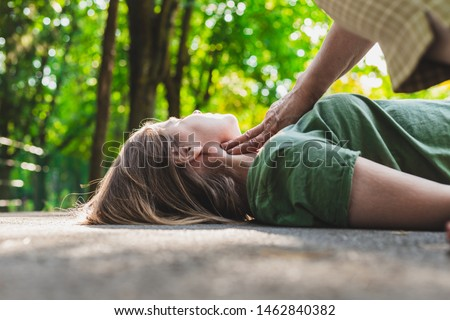 Unconscious fainted girl having pulse checked by an old woman – Teenager lying on the ground while her pulse is verified by an elder citizen on teen's carotid artery