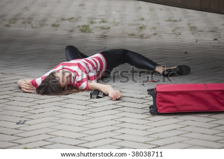 Unconscious woman lying on asphalt road stock photo