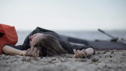 Unconscious woman lying on seashore, drowned swimmer, victim of shipwreck