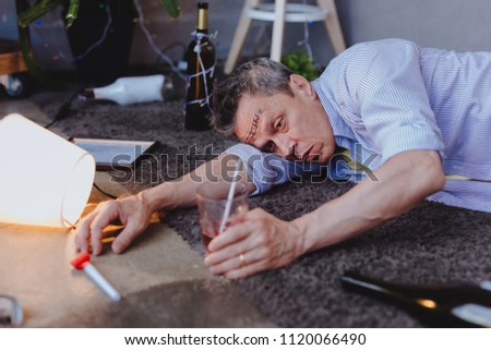 Uncontrollable desire. Gloomy mature man locating on floor and desiring cocktail #1120066490