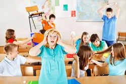 Uncontrollable pupils in classroom acting out, frustrated teacher tearing a hair out.