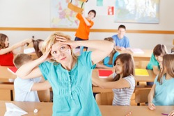 Uncontrollable pupils in classroom acting out, frustrated teacher