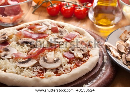 Uncooked Bacon and Mushroom Pizza with Ingredients at the Back